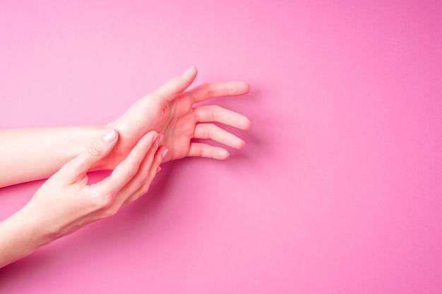 Lindas mãos femininas mostrando manicure fofa fresca, conceito de cuidados com a pele e as unhas, fundo rosa