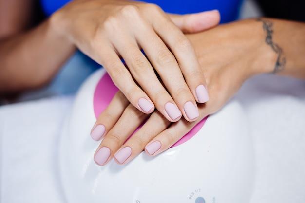 Lindas mãos femininas processo de fabricação de tratamento de unhas de dedo broca de lima de unha profissional em ação conceito de beleza e cuidados com as mãos