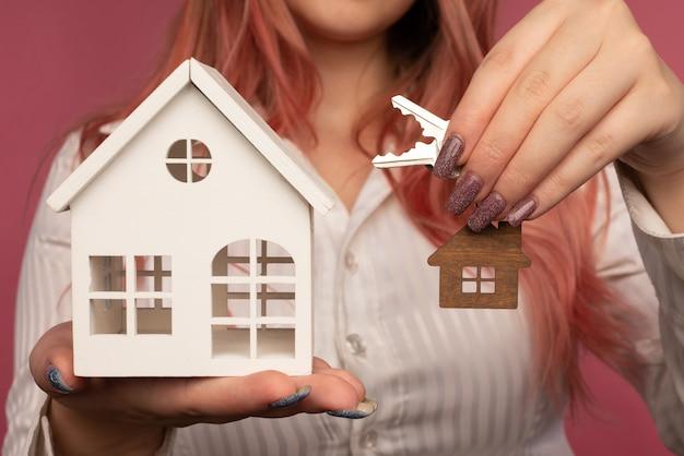 Lindas mãos femininas segurando as chaves e uma casa ao fundo