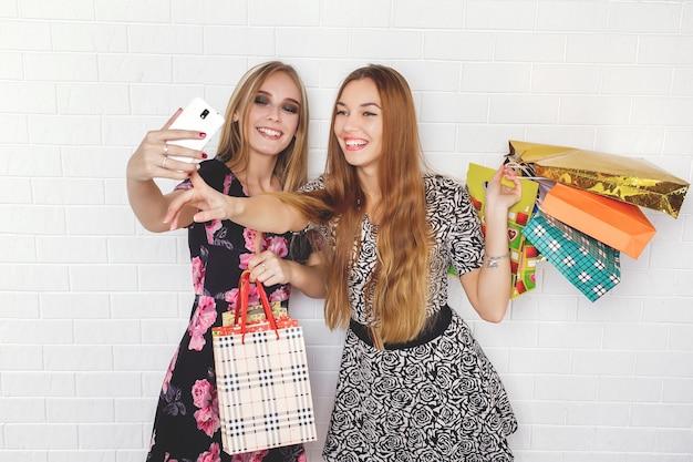 Lindas meninas adolescentes carregando sacolas de compras
