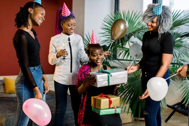 Lindas meninas afro-americanas com balões e chapéus comemoram aniversário e dão presentes de aniversário.