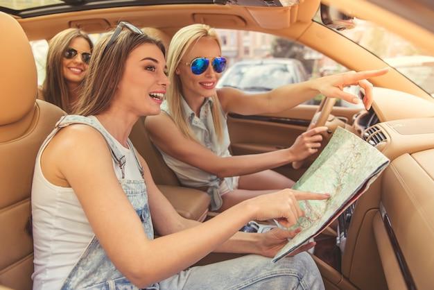 Lindas meninas elegantes estão estudando o mapa