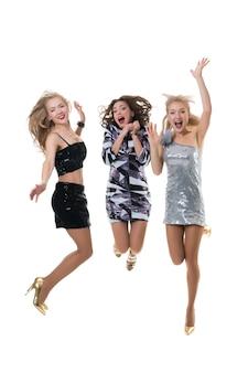 Lindas meninas felizes estão pulando no estúdio