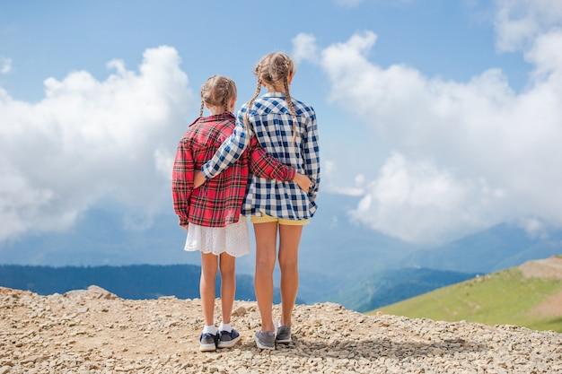 Lindas meninas felizes nas montanhas no nevoeiro