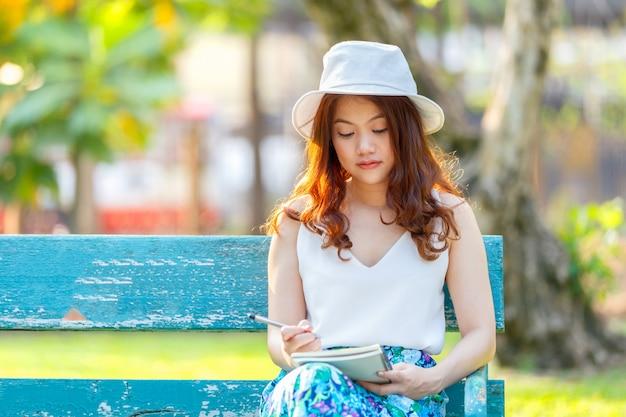 Lindas mulheres asiáticas com caneta escrevendo caderno e sentado num banco de madeira e em um parque