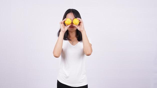 Lindas mulheres asiáticas com um limão isolado na superfície branca