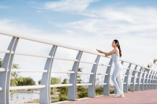 Lindas mulheres asiáticas em roupas esportivas, ouvindo música durante o exercício ao ar livre no parque. conceito de mulheres saudáveis. treino de corrida.