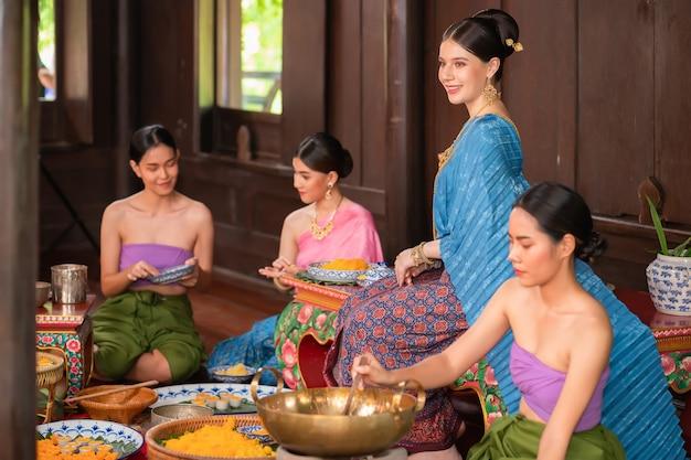 Lindas mulheres asiáticas em tailandês, vestidas com trajes tradicionais tailandeses e fazendo sobremesas na cozinha com o patrão, a filha e a criada. no conceito de vida no passado do ayutthaya