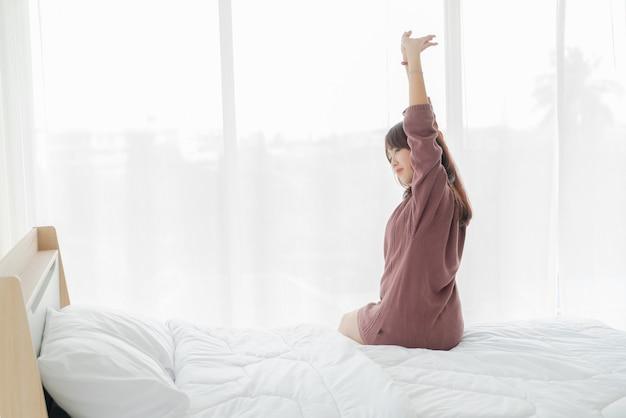 Lindas mulheres asiáticas na cama e acordando de manhã