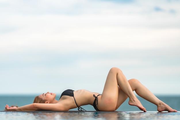 Lindas mulheres asiáticas ou tailandesas e biquínis pretos no bar, relaxando na praia para viajar no conceito de verão