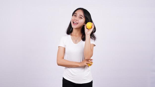 Lindas mulheres asiáticas pensando com um limão isolado na superfície branca