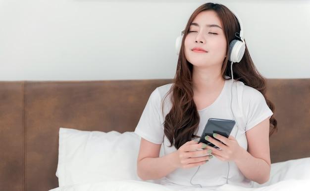 Lindas mulheres asiáticas usando fones de ouvido, ouvindo música em streaming de seus smartphones. na cama no quarto branco