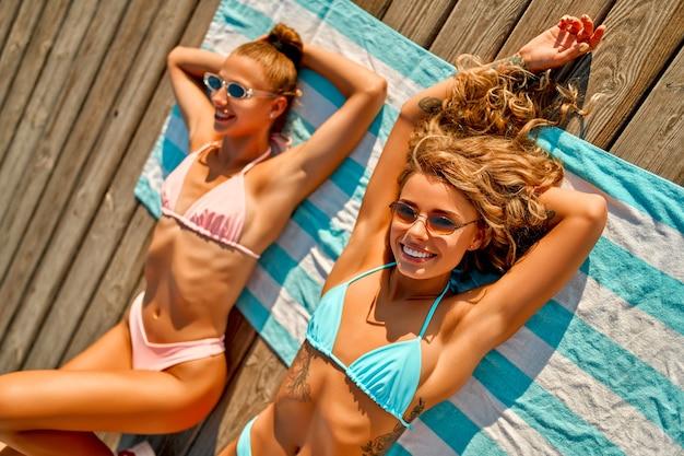 Lindas mulheres brancas em óculos de sol e maiôs estão tomando sol na praia, curtindo as férias.