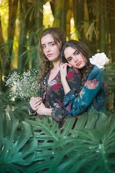 Lindas mulheres cercadas por folhas de monstera