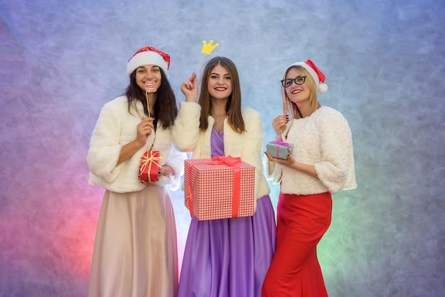 Lindas mulheres com caixas de presente em vestidos de noite da moda e chapéus de papai noel