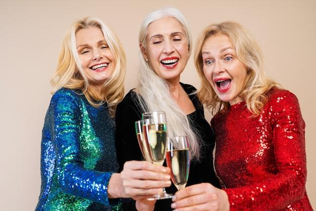 Lindas mulheres idosas com vestido festivo elegante se divertindo em uma festa