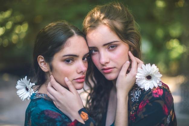 Lindas mulheres segurando flores e abraçando