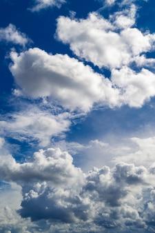 Lindas nuvens brancas em um semicírculo contra o céu azul.