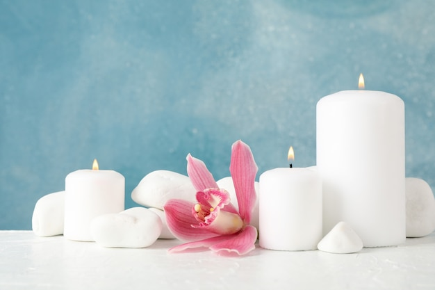 Lindas orquídeas, velas e pedras spa na mesa branca