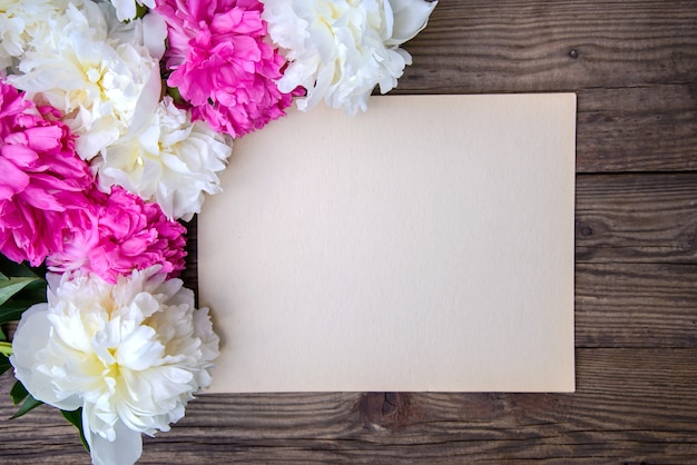 Lindas peônias brancas e rosa e uma folha de papel em uma superfície de madeira