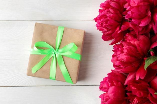Lindas peônias de flores cor de rosa brilhantes e caixa de presente em um fundo branco de madeira. vista do topo.