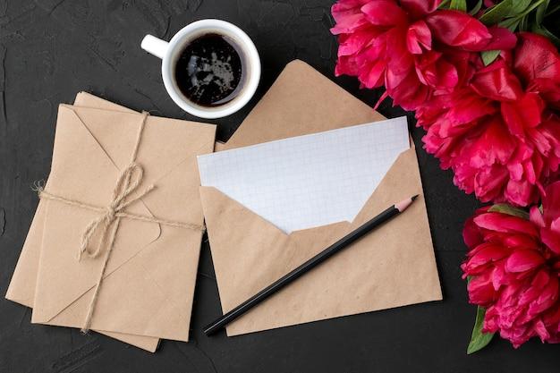 Lindas peônias de flores cor de rosa brilhantes e uma pilha de envelopes e café em um fundo preto de grafite. vista do topo.