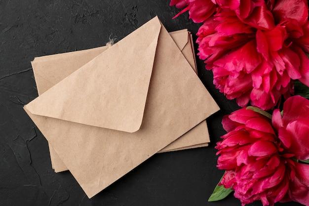 Lindas peônias de flores cor de rosa brilhantes e uma pilha de envelopes em um fundo preto de grafite. vista do topo.