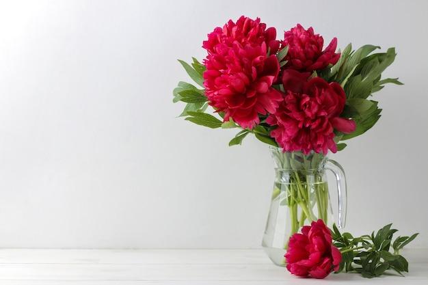 Lindas peônias de flores cor de rosa brilhantes em uma jarra sobre um fundo claro. espaço para texto