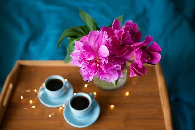 Lindas peônias rosa e duas xícaras de café estão de pé em uma bandeja de madeira na cama. fechar-se. vista de cima.