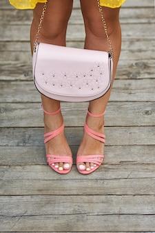 Lindas pernas bronzeadas de uma garota com sandálias coral e saltos segurando uma bolsa no chão de madeira