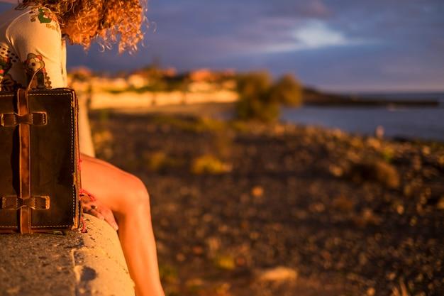 Lindas pernas e cabelos cacheados de mulher jovem descansando sentada em um banco perto da costa e da costa do oceano