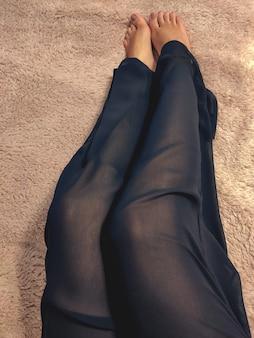 Lindas pernas femininas em calças pretas de seda clara deitadas na cama em um cobertor bege macio