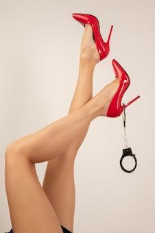 Lindas pernas femininas longas e sensuais em sapatos vermelhos de salto alto com algemas levantadas