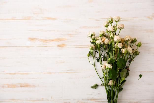 Lindas rosas brancas na mesa de madeira