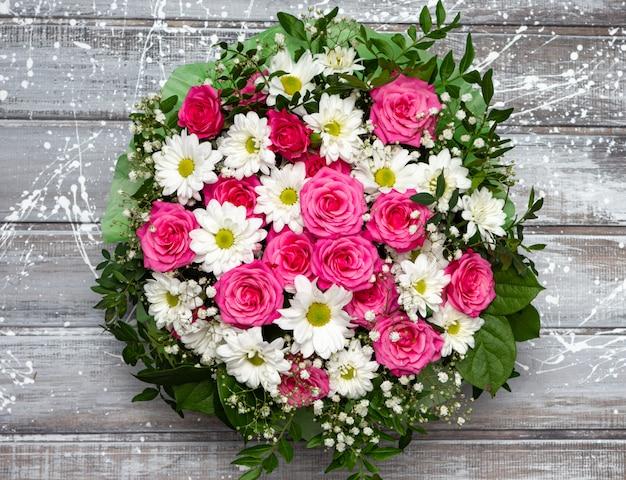 Lindas rosas cor de rosa e margaridas brancas em uma caixa sobre um fundo cinza de madeira.