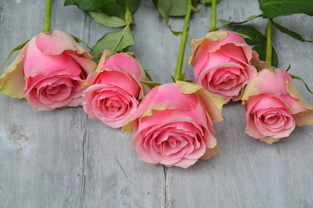 Lindas rosas cor de rosa em uma superfície de madeira
