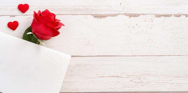 Lindas rosas e forma de coração com cartão vazio branco isolado em uma mesa de madeira brilhante, cópia espaço, vista plana, vista superior, simulação