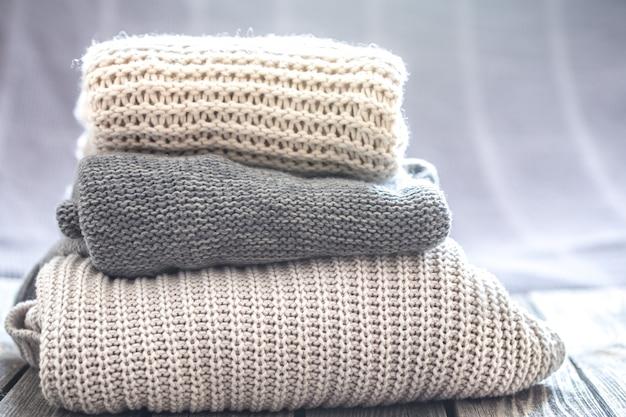 Lindas roupas de malha, suéteres artesanais dobrados, close-up e bem-feitos.