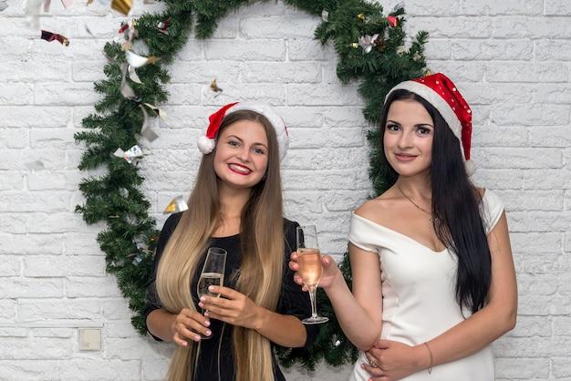 Lindas senhoras com champanhe e gorros de papai noel