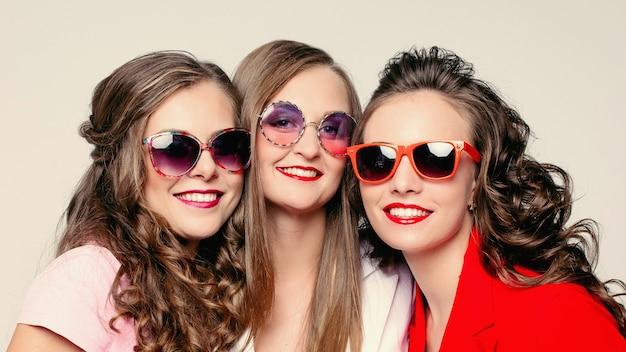 Lindas senhoras felizes em elegantes óculos de sol e jaquetas.
