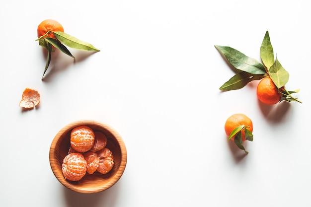 Lindas tangerinas maduras com folhas verdes em uma placa de madeira