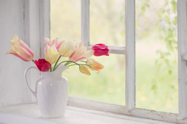 Lindas tulipas em um vaso no parapeito da janela branca