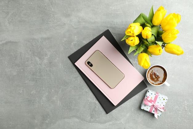 Lindas tulipas em vaso e smartphone com acessórios em cinza, vista superior