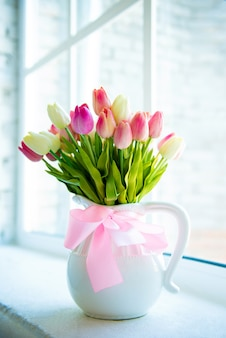Lindas tulipas heterogêneas em um vaso branco contra a janela. buquê de tulipas papagaio tulipas rosa vaso branco peitoril de janela