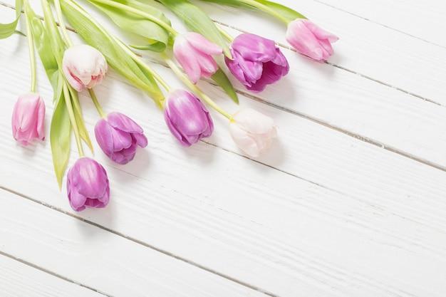 Lindas tulipas na superfície de madeira branca