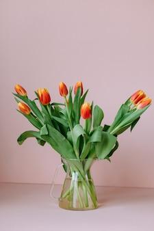 Lindas tulipas vermelhas em um fundo rosa claro que uma florista europeia prepara um buquê de tulipas para