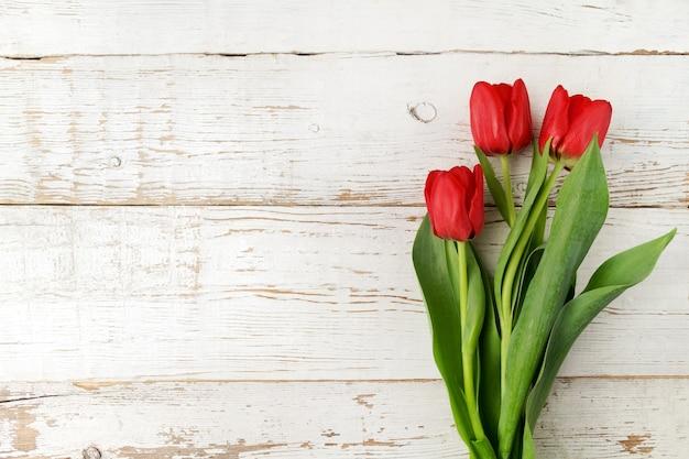 Lindas tulipas vermelhas na mesa de madeira