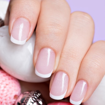 Lindas unhas de mulher com linda manicure francesa branca