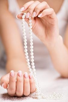 Lindas unhas de mulher com linda manicure francesa e pérolas brancas