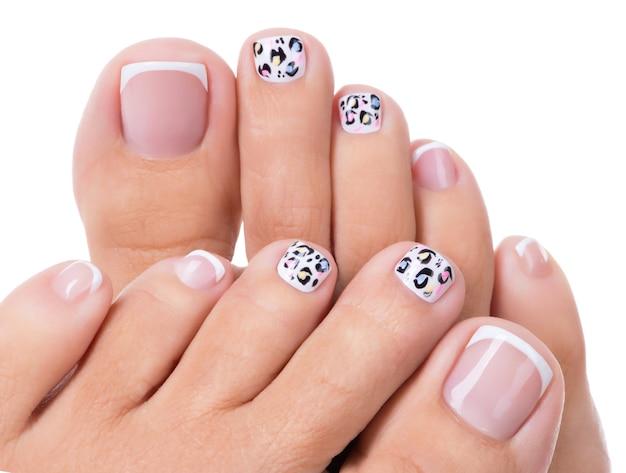 Lindas unhas femininas das pernas com bela manicure francesa e arte